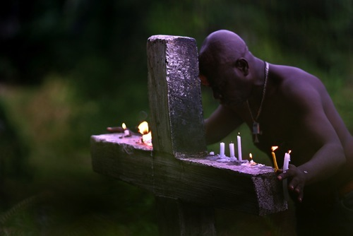 At Vodou Pilgrimage in the south of Haiti a man prays at Baron Samedi cross before entering sacred water fall and pool.